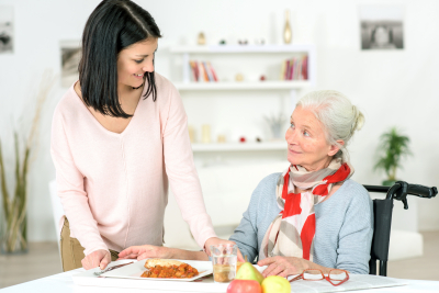 caregiver preparing a meal to the senior woman
