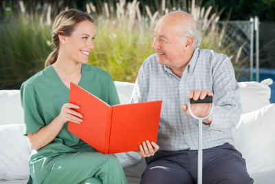 caregiver and senior man are smiling while reading a book